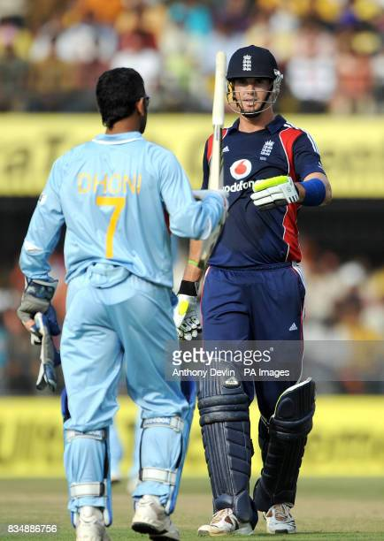 India's MS Dhoni hands England's Kevin Pietersen his bat after he let go of it midshot during the Second One Day International at the Nehru Stadium...