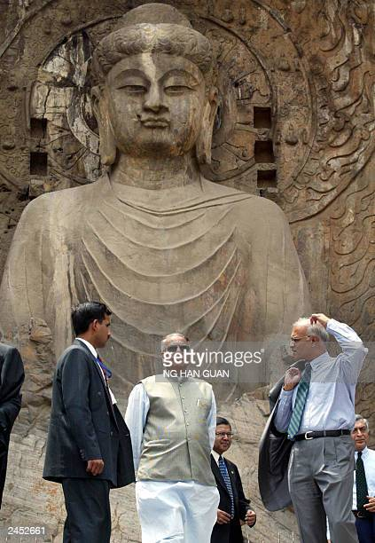 India's Foreign Minister Yashwant Sinha walks near a giant sculpture of the buddha during a visit to Luoyang with India's Premier Atal Bihari...