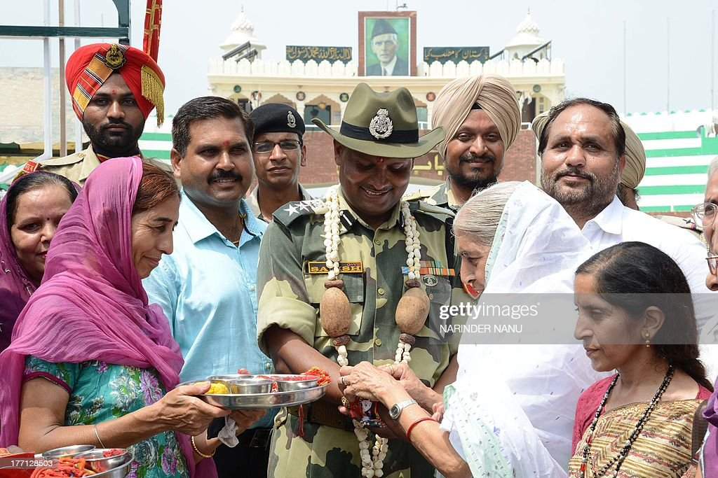 India's former Punjab state Minister for Social Security, Women and Child Welfare, Laxmi Kanta Chawla (3R) ties a sacred thread or rakhi onto the wrists of Indian Border Security Force (BSF) Commandant, Satish Kumar (C) during the Raksha Bandhan festival at the India-Pakistan Wagah Border post on August 21, 2013. The ceremony topically involves a bracelet being tied by a sister to her brother's wrist, symbolising the sister's love and prayers for her brother's well-being, and the brother's vow to protect her.