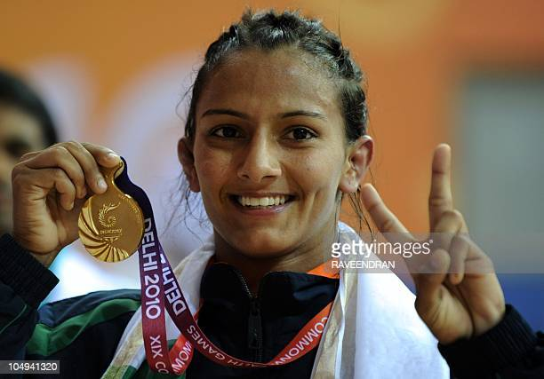 India's Geeta celebrates with her gold medal after defeating Australia's Emily Bensted in the women's wrestling 55 kg final at the XIX Commonwealth...