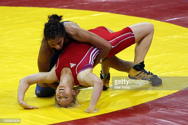 India's Geeta challenges Australia's Emily Bensted during their 55kg women's freestyle wrestling match at the Commonwealth Games in New Delhi October...