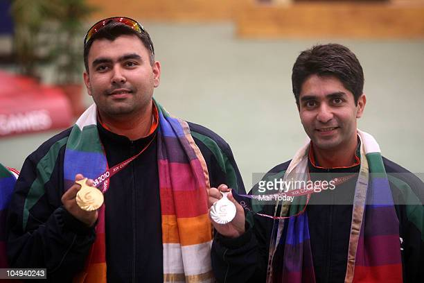 India's gold winner Gagan Narang left and compatriot silver medalist Abhinav Bindra shows their medals after the medal award ceremony for the men's...