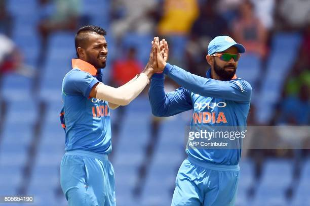 India's Hardik Pandya celebrates with team captain Virat Kohli after dismissing West Indies' Jason Mohammed during the fourth One Day International...