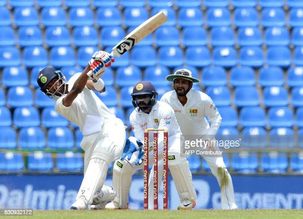 India's Hardik Pandya plays a shot as Sri Lanka's Niroshan Dickwella and Dimuth Karunaratne look on during the second day of the third and final Test...