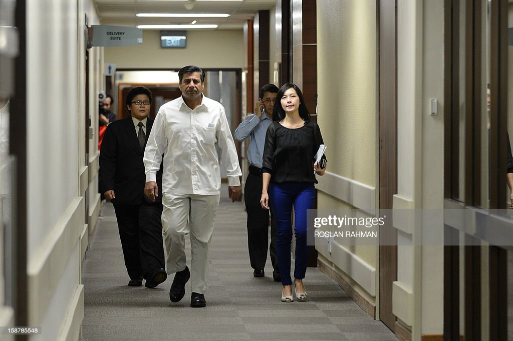 India's high commissioner to Singapore T.C.A Raghavan (2ndL) walks along the corridor to speak to journalists at the Mount Elizabeth hospital after the announcement of the death of the Indian gang-rape victim, in Singapore on December 29, 2012. The victim, 23, died Saturday in Singapore after suffering severe organ failure, the hospital treating her said, in a case that sparked widespread street protests over violence against women. AFP PHOTO/ROSLAN RAHMAN