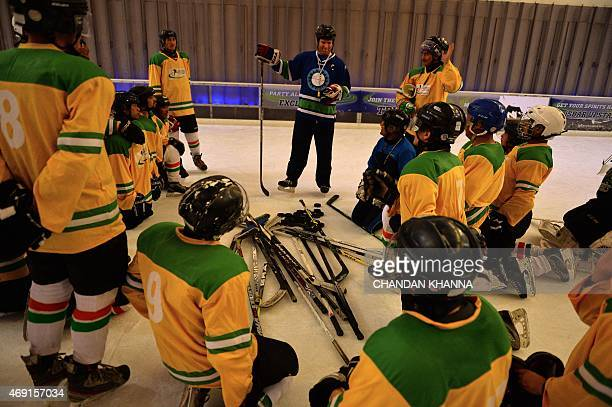 India's ice hockey team coach Adam Sherlip talks to players during a practice session inside an ice skating bar and café in a mall in Gurgaon on the...