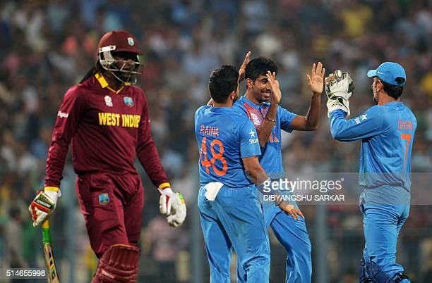 India's Jasprit Bumrahcelebrates with teammates captain Mahendra Singh Dhoniand Suresh Rainaafter the dismissal of West Indies's batsman Chris...