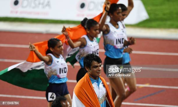 India's javelin athlete Neeraj Chopra and India's women's 4 x 400m relay team celebrate placing first during the final day of the 22nd Asian...