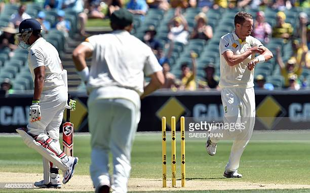 India's Karn Sharma leaves the crease after being clean bowled by Australia's paceman Peter Siddle on the fourth day of the first Test cricket match...