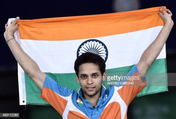 India's Kashyap Parupalli holds his national flag as he celebrates beating Singapore's Derek Wong in the men's singles badminton gold medal final...