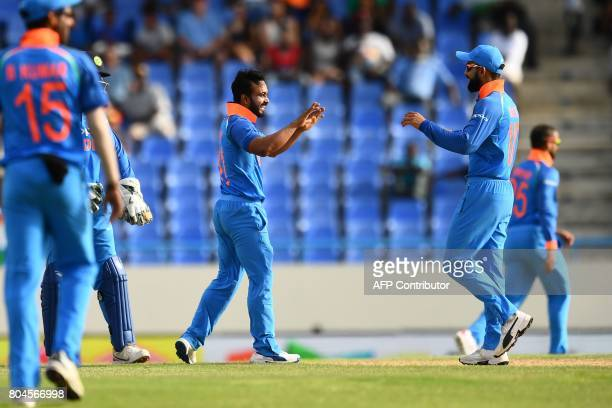 India's Kedar Jadhav celebrates with team captain Virat Kohli after dismissing West Indies' Kesrick Williams during the third One Day International...
