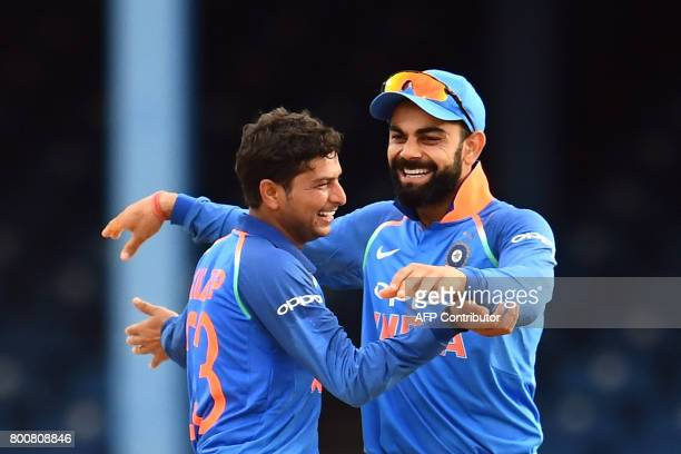 India's Kuldeep Yadav celebrates with team captain Virat Kohli after dismissing West Indies' captain Jason Holder during the second One Day...