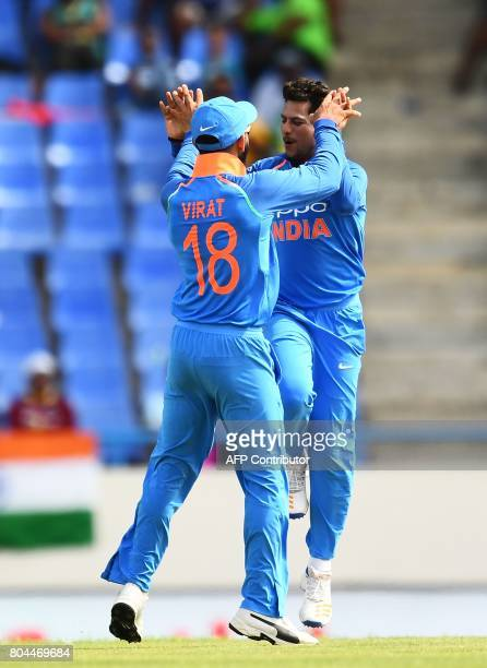 India's Kuldeep Yadav celebrates with team captain Virat Kohli after bowling out West Indies' Roston Chase during the third One Day International...
