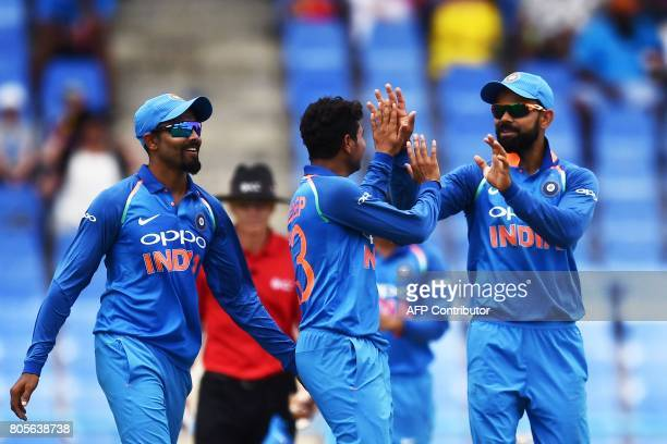 India's Kuldeep Yadav celebrates with team captain Virat Kohli and teammate Ravindra Jadeja after bowling out West Indies' Roston Chase during the...