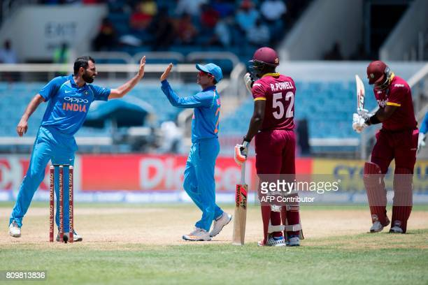 India's Kuldeep Yadav celebrates with teammate Mohammed Shami after catching out West Indies' batsman Ashley Nurse during the fifth One Day...