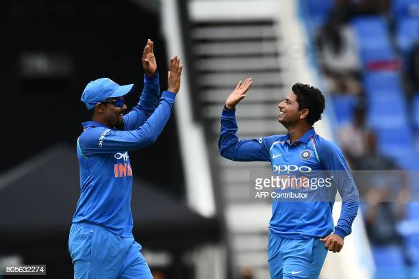 India's Kuldeep Yadav celebrates with teammate Ravindra Jadeja after bowling out West Indies' Roston Chase during the fourth One Day International...