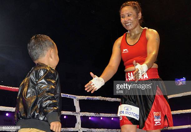 India's Laishram Sarita Devi shares a moment with her son after winning her fight against Hungarys Zsofia Bedo during their IBC Pro Boxing match on...