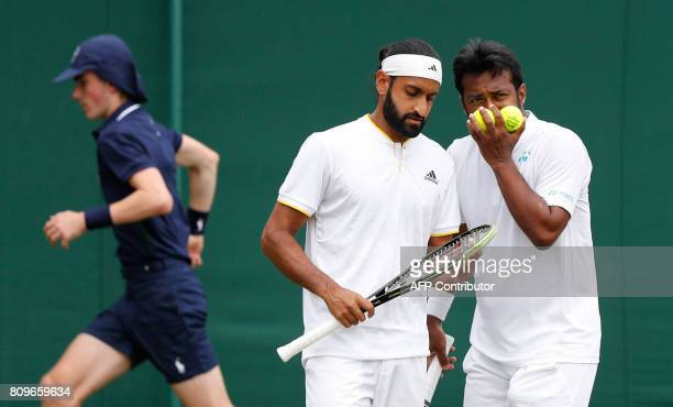 India's Leander Paes and his partner Canada's Adil Shamasdin confer between points against Austria's Julian Knowle and Philipp Oswald during their...