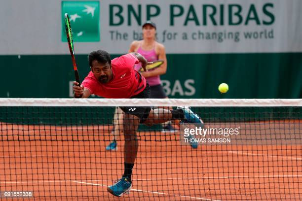 India's Leander Paes and Switzerland's Martina Hingis return the ball to Slovenia's Katarina Srebotnik and South Africa's Raven Klassen during their...