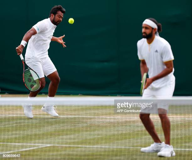 India's Leander Paes returns as his partner Canada's Adil Shamasdin stands ready at the net during their men's doubles first round match against...
