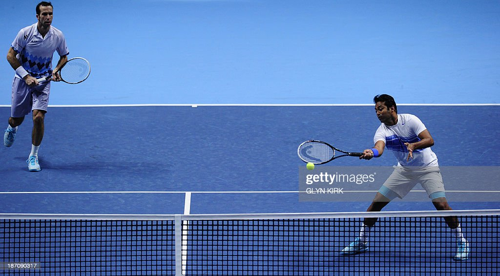 India's Leander Paes (R) returns at the net as his partner Czech Republic's Radek Stepanek (L) covers the back of the court against Spain's Fernando Verdasco and as his partner Spain's David Marrero during their group B doubles match in the round robin stage on the third day of the ATP World Tour Finals tennis tournament in London on November 6, 2013.