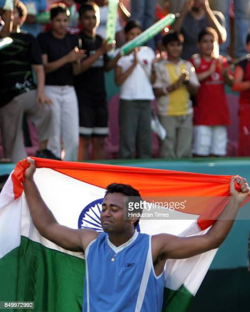 India's Leander Paes waves national flag after beating Aqeel Khan in the 5th singles match of the Asia Oceana Group 1 playoff tie at the Brabourne...