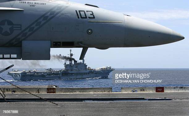 India's lone aircraft carrier the INS Viraat sails alongside a US fighter plane on the US supercarrier Kitty Hawk in the Bay of Bengal during the...