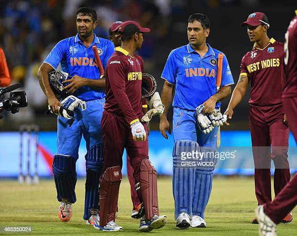 India's Mahendra Singh Dhoni and teammate Ravichandran Ashwin lead players off the ground after their win in the 2015 Cricket World Cup Pool B match...