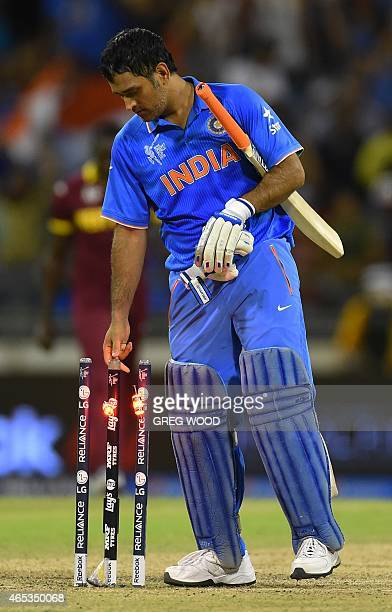 India's Mahendra Singh Dhoni lifts the bails off after winning the 2015 Cricket World Cup Pool B match between India and the West Indies in Perth on...
