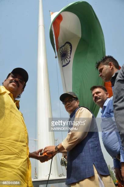 India's Minister of State for Home Affairs Kiren Rijiju poses with Member of Parliament Shwait Malik as he pushes a switch to unfurl a giant national...