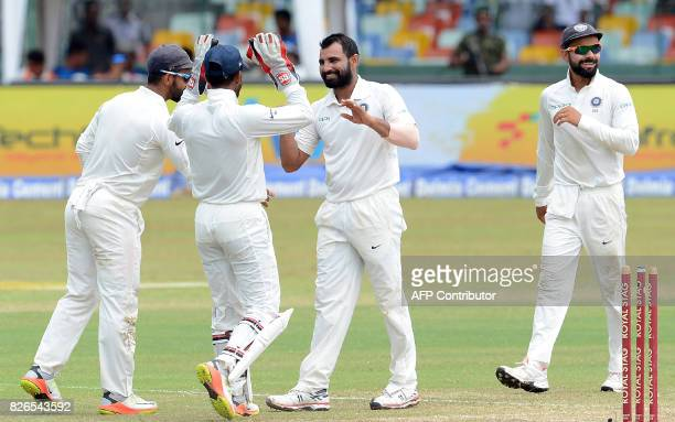 India's Mohammed Shami celebrates with his teammates after he dismissed Sri Lanka's Niroshan Dickwella during the third day of the second Test...