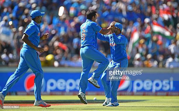 India's Mohit Sharma celebrates with teammates after taking a catch to dismiss West Indies batsman Chris Gayle during the 2015 Cricket World Cup Pool...