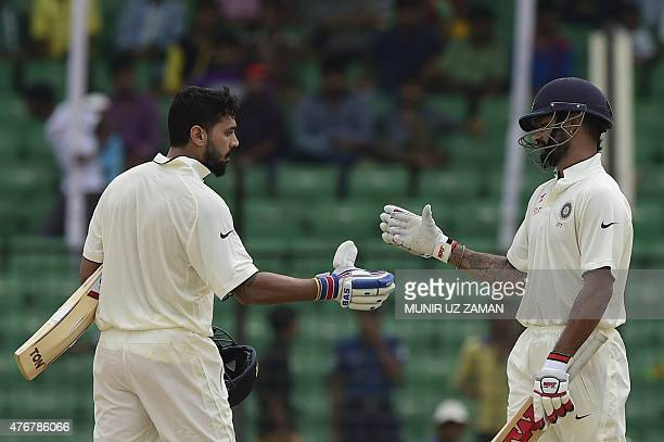 India's Murali Vijay celebrates his century with teammate Shikhar Dhawan during the third day of the cricket Test match between Bangladesh and India...