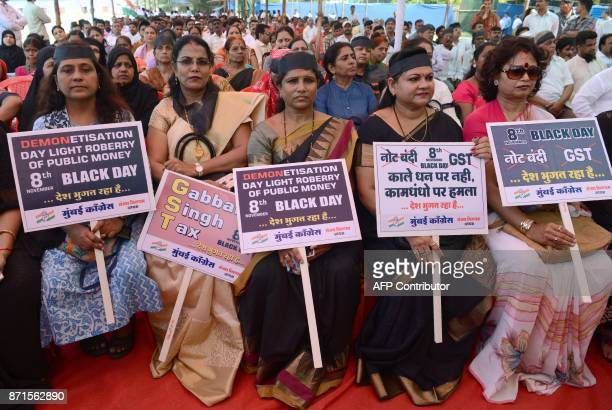 India's National Congress Party supporters hold placards during a protest on the first anniversary of India's demonetisation scheme in Mumbai on...
