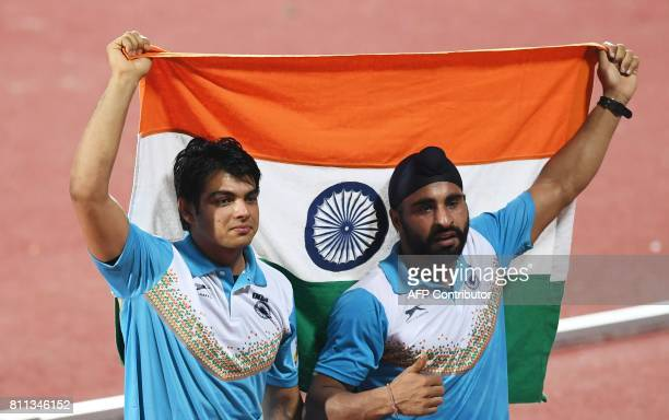 India's Neeraj Chopra and Davinder Singh Kang celebrate after placing first and third respectively in the javelin throw event during the final day of...