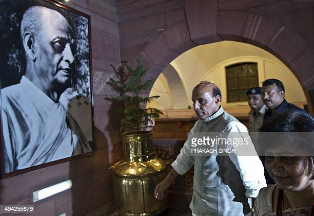 India's new Home Minister Rajnath Singh walks past a photograph of independent India's first Home Minister Sardar Vallabhbhai Patel as he arrives to...