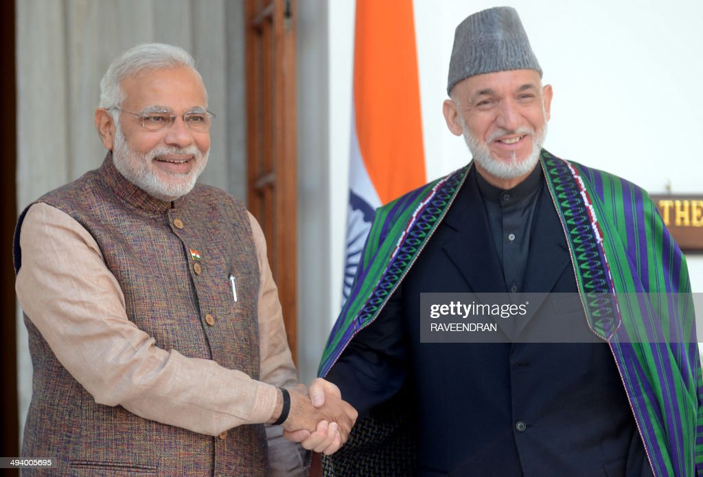 India's newly swornin Prime Minister Narendra Modi shakes hands with Afghanistan President Hamid Karzai during a meeting in New Delhi on May 27 2014...