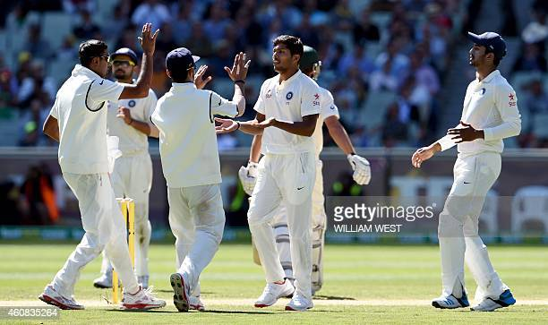 India's paceman Umesh Yadav is congratulated by teammates after dismissing Australia's batsman Joe Burns on the first day of the third cricket Test...