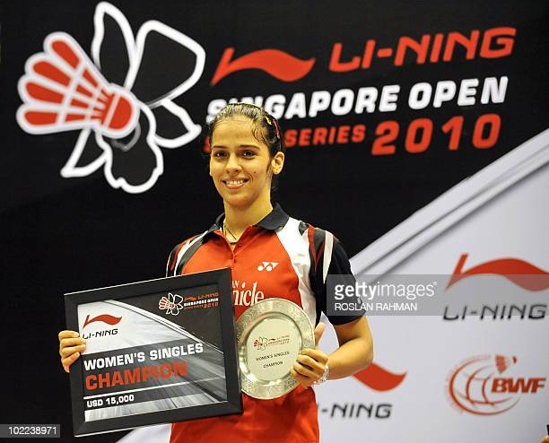 India's player Saina Nehwal poses with the plaque and 15000 US dollar cheque after defeating Taiwan's Tai Tzu Ying during a women's single final of...