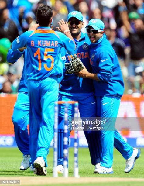 India's players Mahendra Dhoni and Suresh Raina celebrate Pakistan's Mohammad Hafeez wicket bowled B Kumarcaught C Dhoni for 27 during the ICC...