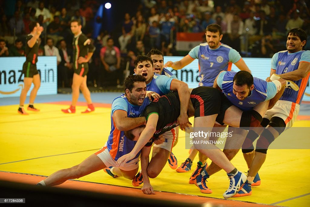 India's players vie with Iran's players during the final match of the Kabaddi World Cup 2016 at the Transstadia in Ahmedabad on October 22, 2016. India defeated Iran 38-29. / AFP / Sam PANTHAKY