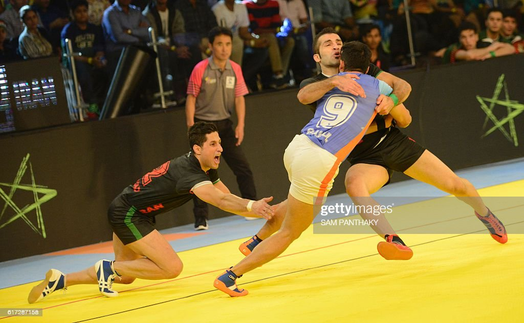 India's players vie with Iran's players during the finals of the Kabaddi World Cup 2016 at the Transstadia in Ahmedabad on October 22, 2016. India defeated Iran 38-29. / AFP / Sam PANTHAKY