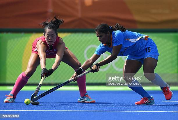 India's Poonam Rani and Japan's Mie Nakashima fight for the ball during the women's field hockey Japan vs India match of the Rio 2016 Olympics Games...