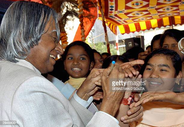 India's President Abdul APJ Kalam autographs the hands of children during a visit to Sadanand Maila Asharam in Bombay 08 February 2004 Kalam had...