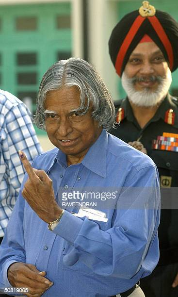 India's President APJ Abdul Kalam smiles as he shows his finger marked with indeible ink to photographers after casting his vote at a polling station...