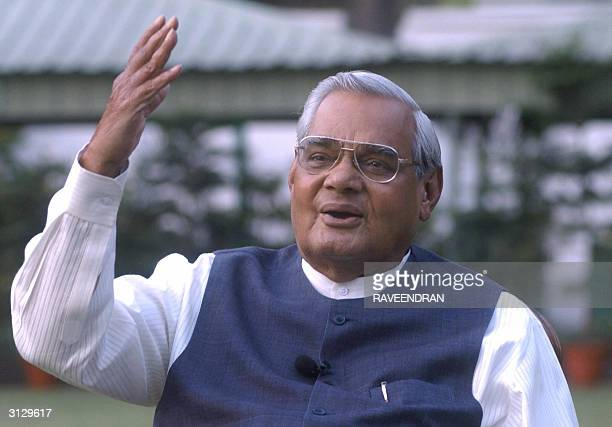 India's Prime Minister Atal Behari Vajpayee gestures as he poses for photographers at his residence in New Delhi 25 March 2004 Vajpayee together with...