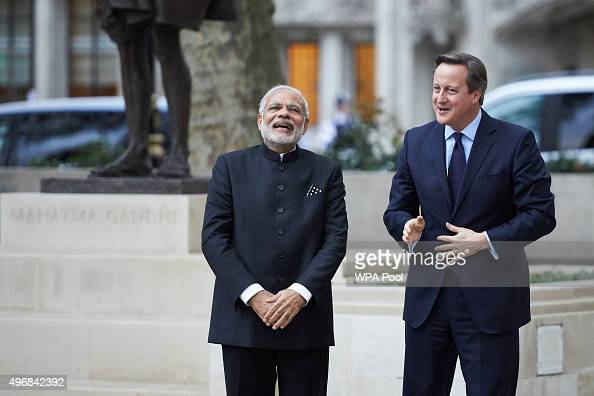 India's Prime Minister Narendra Modi and British Prime Minister David Cameron share a joke in front of a statue of Mahatma Ghandi in Parliament...