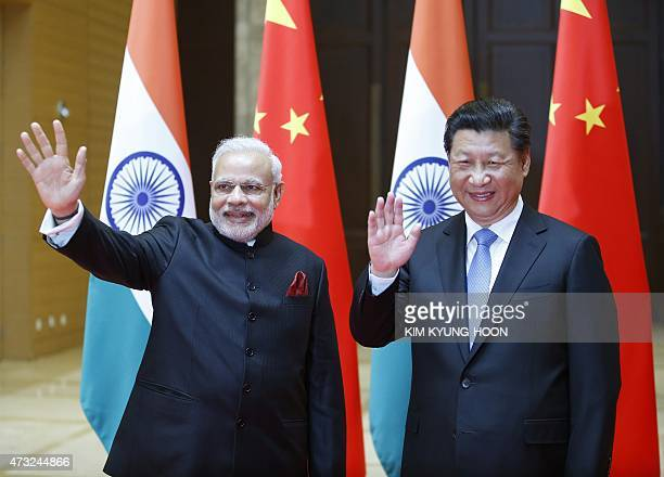 India's Prime Minister Narendra Modi and China's President Xi Jinping wave to journalists before they hold a meeting in Xian in China's Shaanxi...
