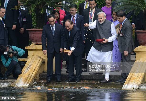 India's Prime Minister Narendra Modi and Vietnamese Prime Minister Nguyen Xuan Phuc feed fish at a pond as they tour the residence of late president...