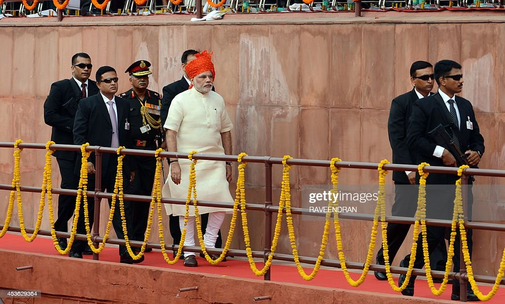 India's Prime Minister Narendra Modi (C) arrives to deliver a speech from the ramparts of the Red Fort in New Delhi on August 15, 2014, to mark the country 68th Independence Day. Modi condemned a spate of rapes as a source of shame for India and urged an end to communal violence on August 15 as he vowed to improve the lives of the nation's poor in his first Independence Day speech.